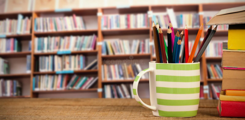 Immagine composita della pila di libri dalla tazza con le matite colorate sulla tavola di legno fotografia stock
