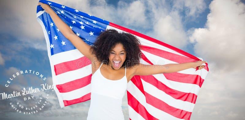 Immagine composita della ragazza incoraggiante graziosa in bandiera americana di tenuta superiore bianca immagine stock
