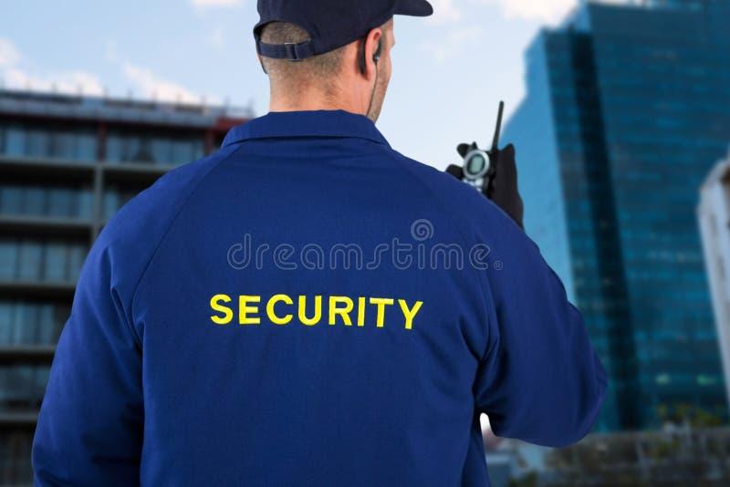 Immagine composita della retrovisione del funzionario di sicurezza che parla sul walkie-talkie fotografia stock