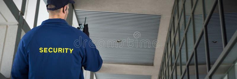 Immagine composita della retrovisione del funzionario di sicurezza che parla sul walkie-talkie immagine stock libera da diritti