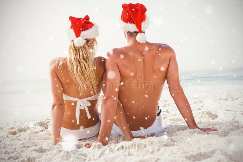 Immagine composita della retrovisione delle coppie che portano il cappello di Santa che si siede insieme alla spiaggia immagini stock libere da diritti