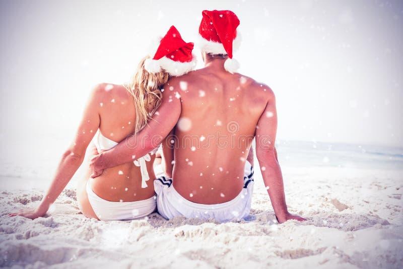 Immagine composita della retrovisione delle coppie con il cappello di Santa che si siede insieme alla spiaggia immagine stock libera da diritti