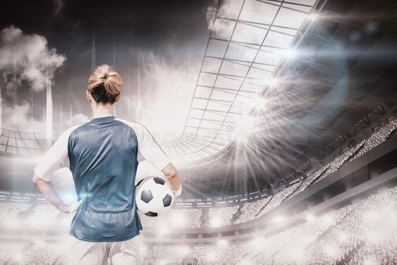 Immagine composita della retrovisione di posa del giocatore di football americano della donna immagine stock libera da diritti