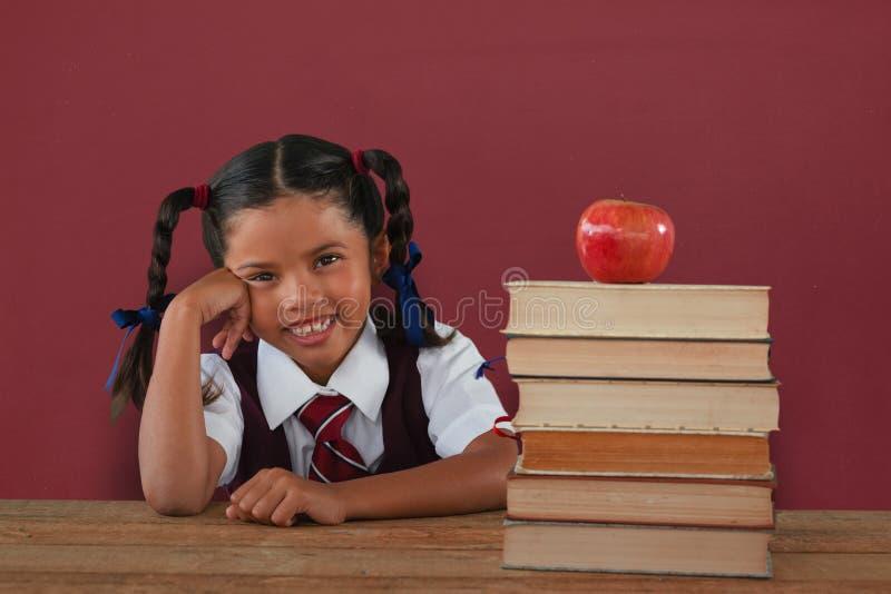 Immagine composita della scolara che pende dai libri e dalla mela sullo scrittorio immagine stock