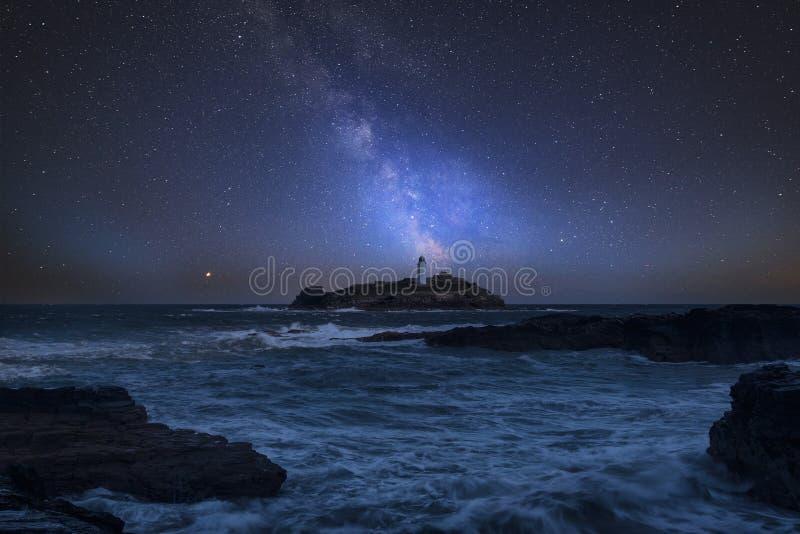 Immagine composita della Via Lattea vibrante sopra paesaggio di Godrevy Ligh fotografia stock libera da diritti