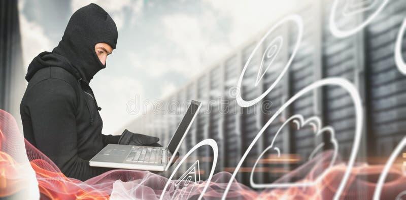 Immagine composita della vista laterale del pirata informatico che per mezzo del computer portatile immagine stock