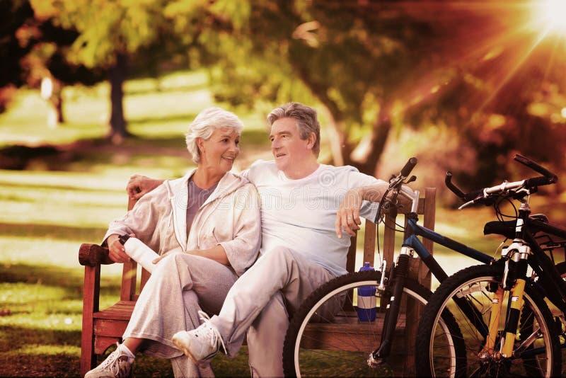 Immagine composita delle coppie anziane con le loro bici fotografie stock libere da diritti