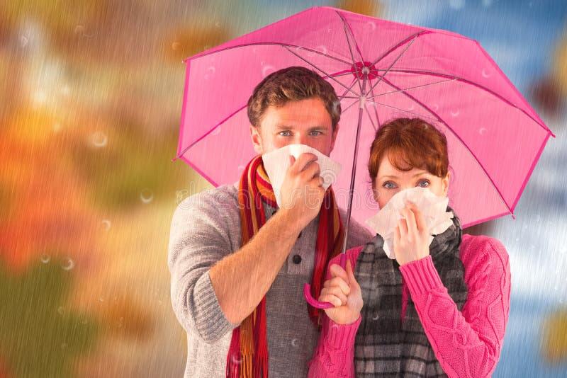 Immagine composita delle coppie che stanno al di sotto di un ombrello fotografia stock libera da diritti
