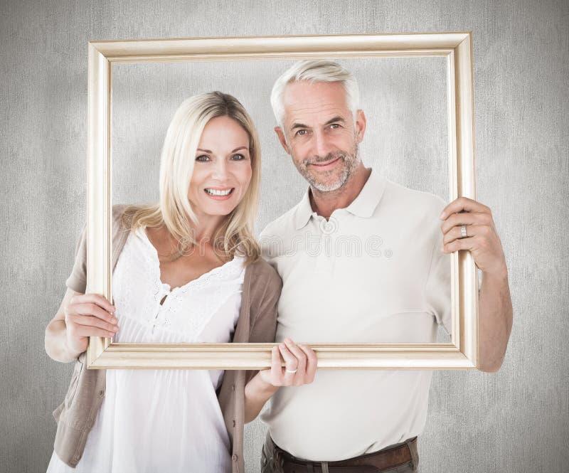 Immagine composita delle coppie felici che tengono una cornice fotografia stock