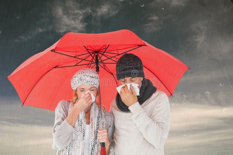 Immagine composita delle coppie malate che starnutiscono nel tessuto mentre stando sotto l'ombrello fotografia stock libera da diritti