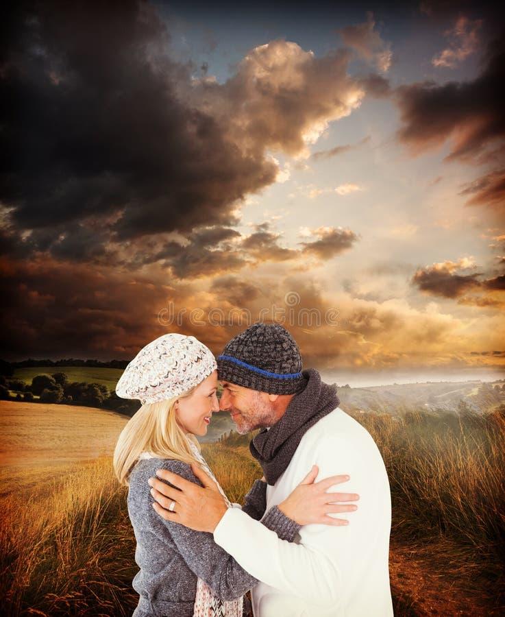 Immagine composita delle coppie sveglie sorridenti che romancing sopra il fondo bianco fotografia stock