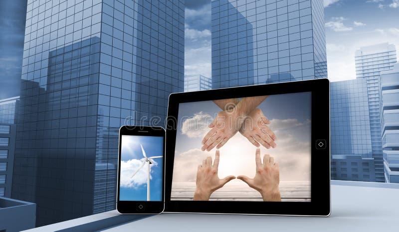 Immagine composita delle mani e del generatore eolico sugli schermi della compressa e dello smartphone fotografia stock libera da diritti