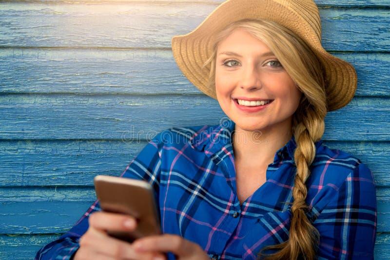 Immagine composita dello smartphone sorridente della tenuta della ragazza immagine stock libera da diritti