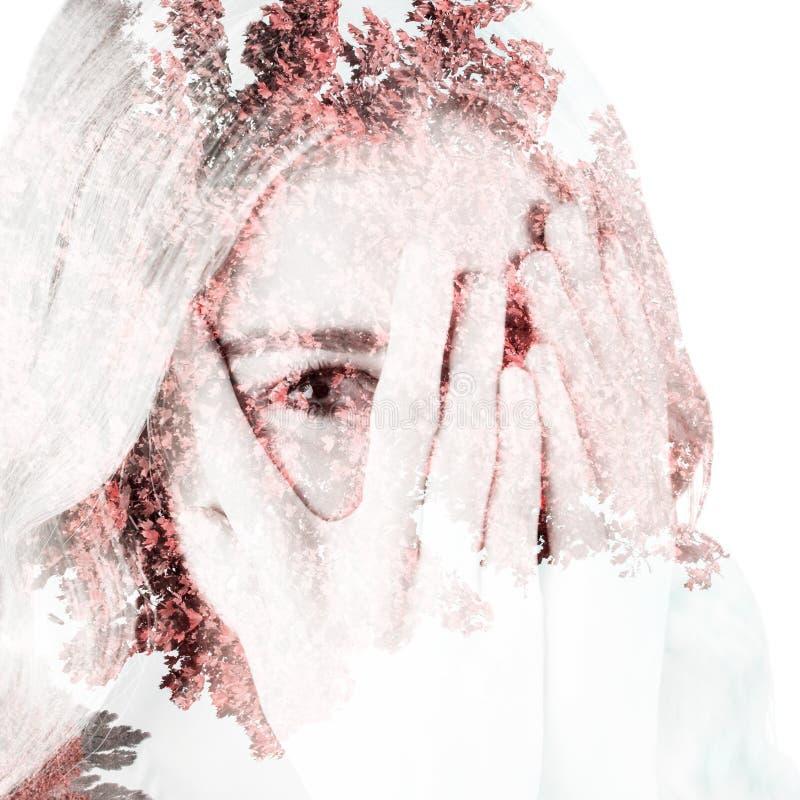 Immagine composita di bella donna bionda che si nasconde dietro le mani fotografia stock