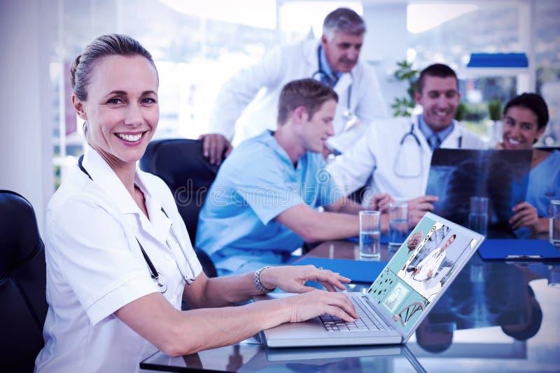 Immagine composita di bello medico sorridente che scrive sulla tastiera con il suo gruppo dietro fotografia stock libera da diritti
