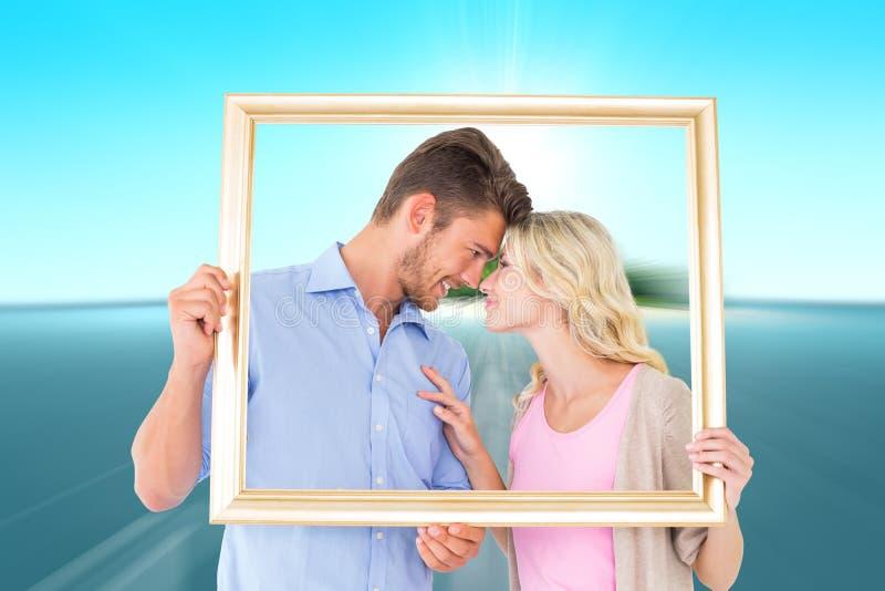 Immagine composita di giovane cornice attraente della tenuta delle coppie immagini stock libere da diritti