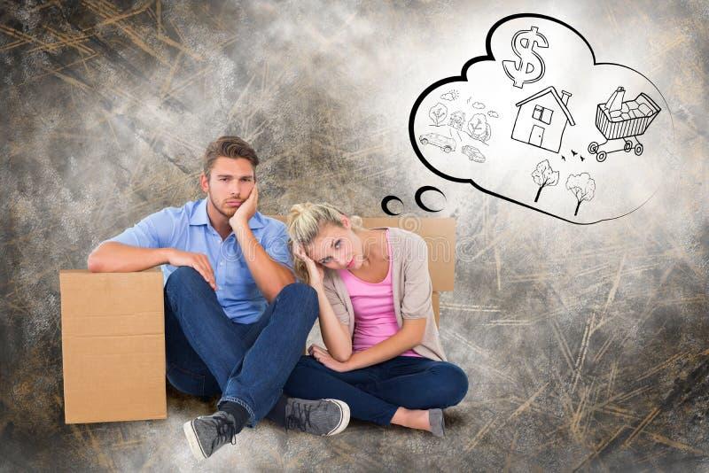 Immagine composita di giovani coppie infelici che si siedono accanto alle scatole commoventi immagini stock