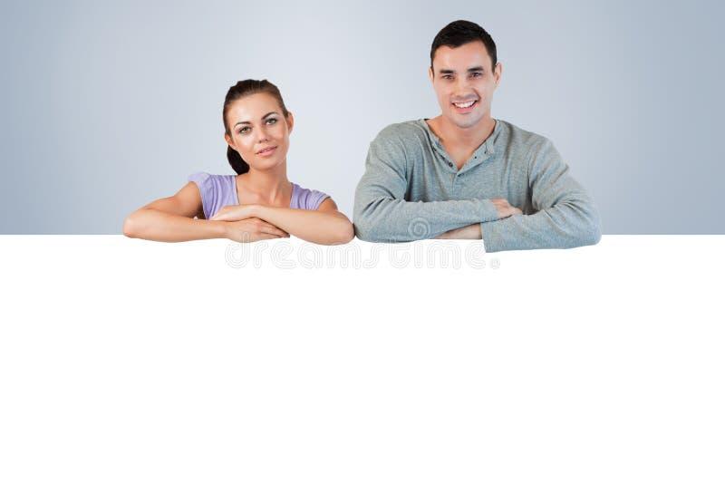 Immagine composita di giovani coppie sorridenti che esaminano una parete immagine stock libera da diritti