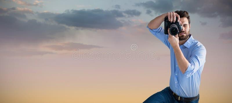 Immagine composita di integrale del fotografo maschio che fotografa tramite la macchina fotografica digitale fotografie stock