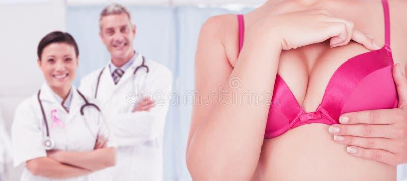 Immagine composita di metà di sezione della donna in seno commovente del reggiseno rosa per consapevolezza del cancro fotografia stock libera da diritti
