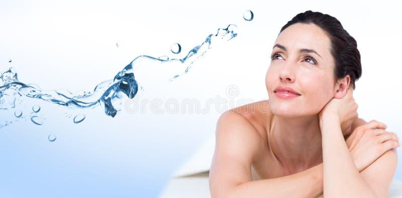 Immagine composita di rilassamento castana sorridente sulla tavola di massaggio immagini stock