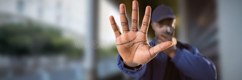 Immagine composita di sicurezza sicura che parla sul walkie-talkie e che fa gesto di arresto fotografie stock