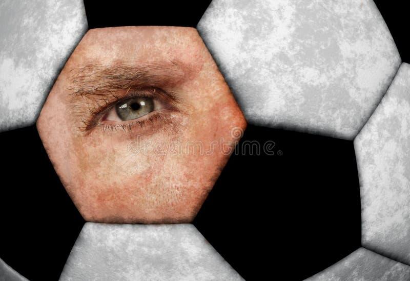 Immagine concettuale del composto dell'occhio azzurro dell'uomo con il pallone da calcio classico di cuoio di struttura nel fan d fotografia stock libera da diritti