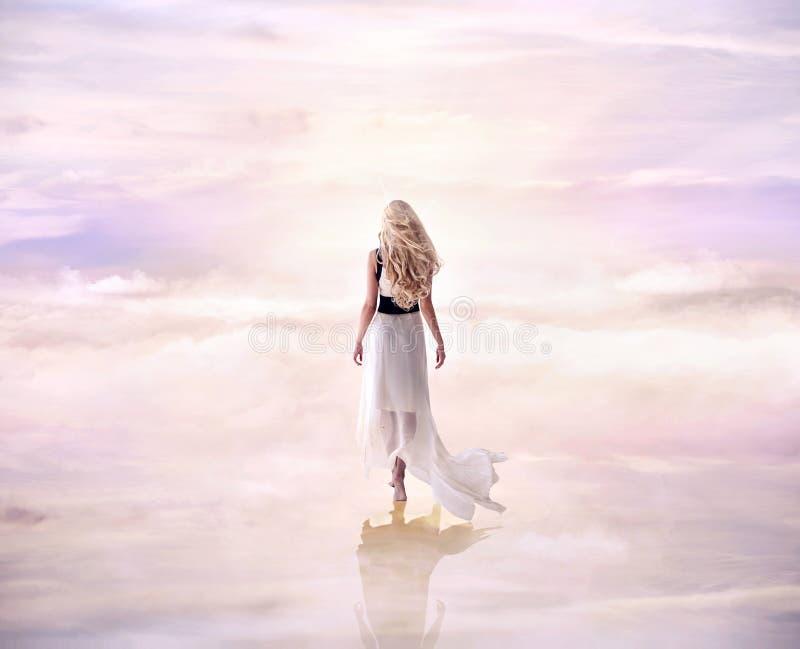 Immagine concettuale di una signora bionda che cammina sul delicato, fluf fotografia stock libera da diritti