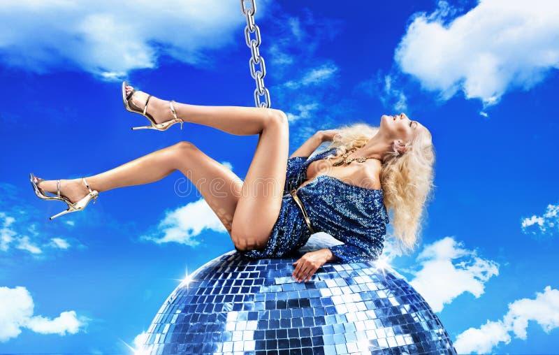 Immagine concettuale di una signora che oscilla sulla palla della discoteca immagini stock libere da diritti