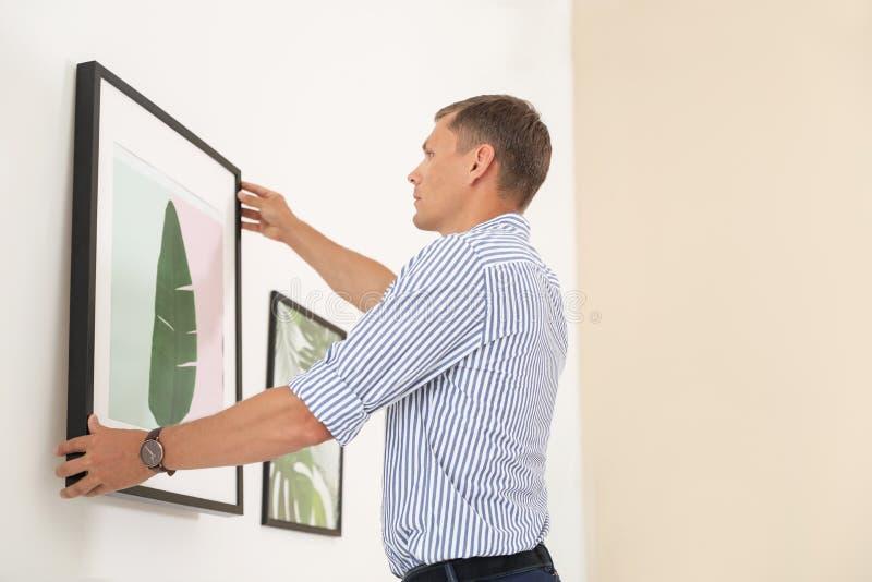 Immagine d'attaccatura dell'uomo bello sulla parete alla mostra fotografia stock