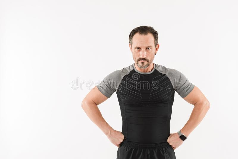 Immagine degli abiti sportivi d'uso atletici dell'uomo 30s che considerano macchina fotografica w fotografia stock