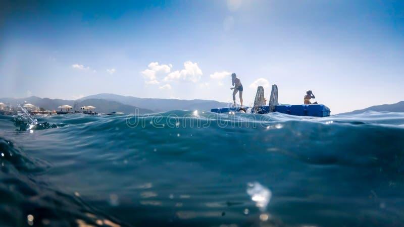 Immagine dei bambini felici che saltano dal pantoon di galleggiamento in mare fotografie stock libere da diritti
