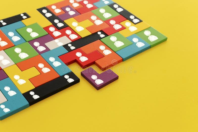 immagine dei blocchetti di puzzle del tangram con le icone della gente sopra la tavola di legno, le risorse umane ed il concetto  immagine stock