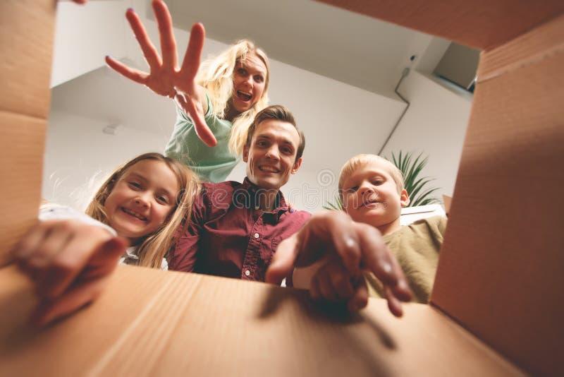 Immagine dei genitori felici e dei bambini che guardano dentro la scatola di cartone immagine stock