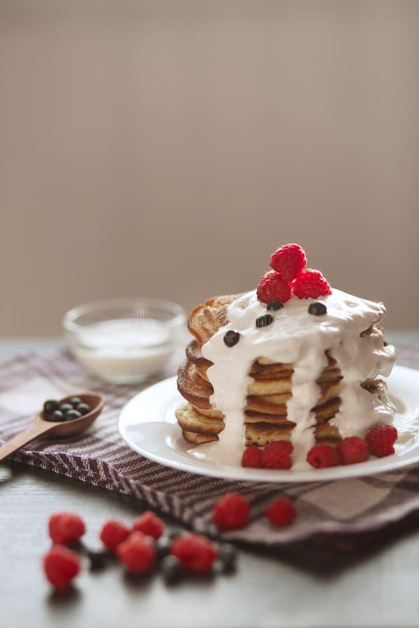 Immagine dei pancake con le bacche e la panna acida Prima colazione deliziosa di estate, pancake classici con la bacca fresca ed  fotografia stock libera da diritti
