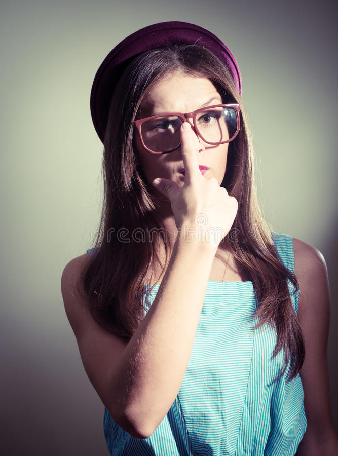 Immagine dei vetri d'uso della bella ragazza contro il fondo leggero della parete immagini stock