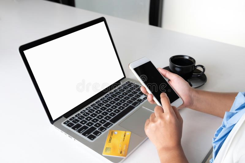 Immagine del capo dell'ufficio della donna di affari che tiene la carta di credito e che per mezzo del computer portatile per l'a fotografia stock libera da diritti