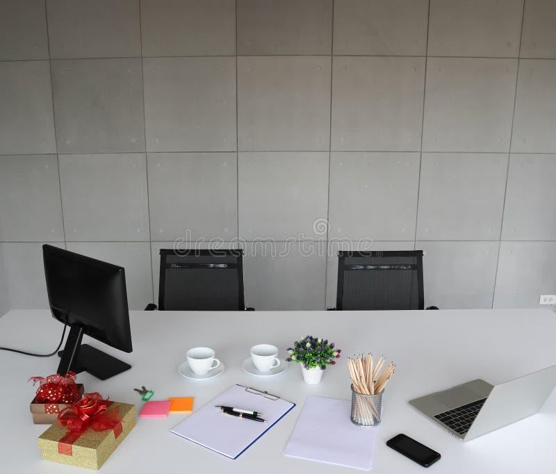 Immagine del computer portatile, telefono cellulare, penne, matite, Libro Bianco sul DES bianco fotografie stock libere da diritti