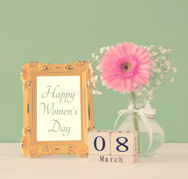 Immagine del concetto internazionale di giorno delle donne con il bello fiore nel vaso sulla tavola di legno fotografia stock libera da diritti