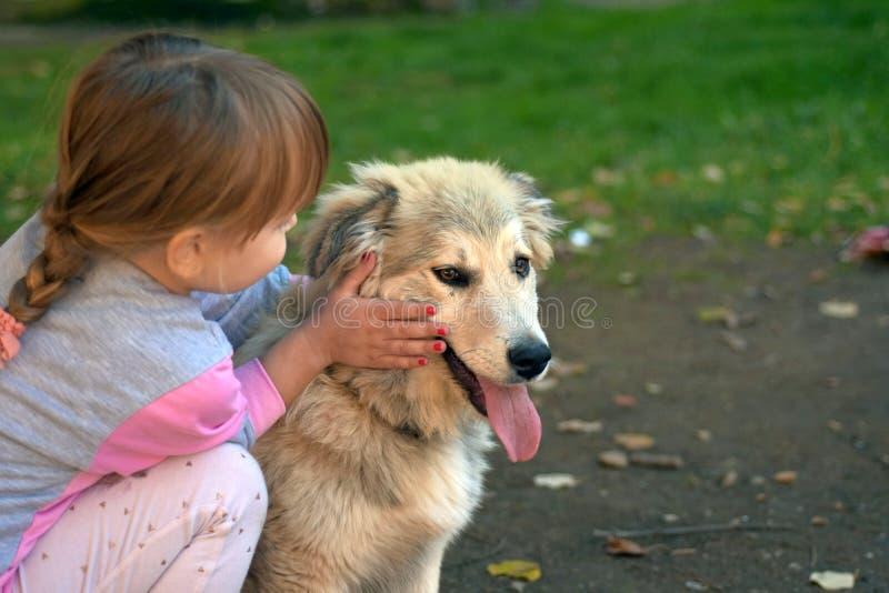Immagine del cucciolo di cane bianco commovente della bambina che mette sulla terra del parco immagini stock