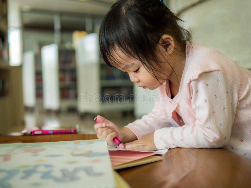 Immagine del disegno della bambina alla tavola sulla carta fotografie stock libere da diritti