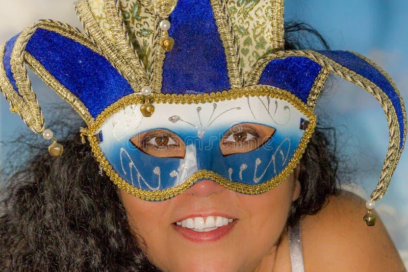 Immagine del fronte di una donna sorridente con capelli ricci neri che indossano una maschera veneziana fotografie stock