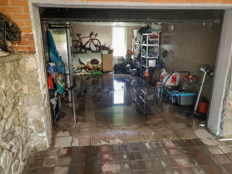 Immagine del garage sommerso dopo pioggia persistente Pavimento bagnato e cosa di galleggiamento in casa dopo l'inondazione fotografia stock libera da diritti