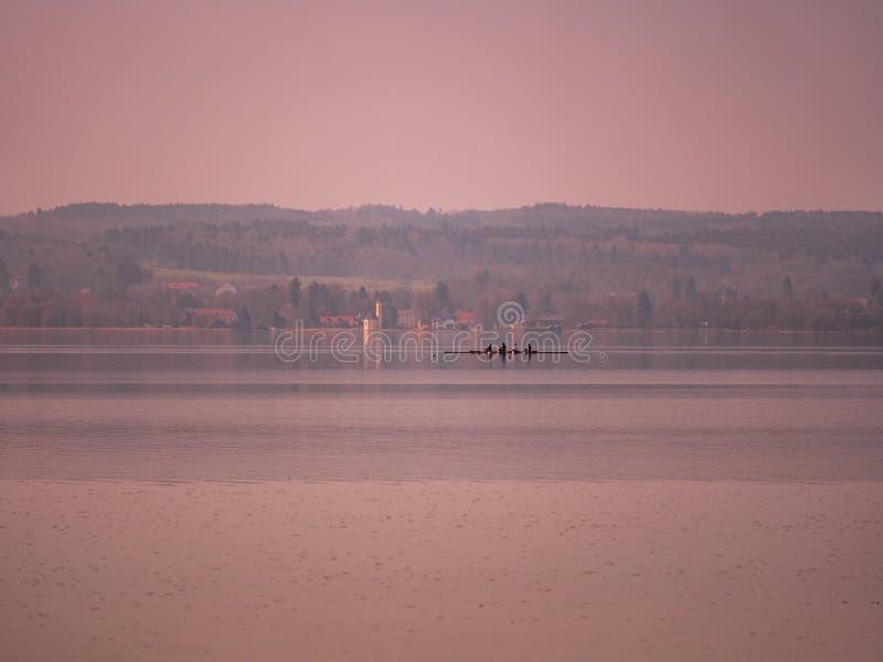 Immagine del lago Ammer con l'imbarcazione a remi e del villaggio con la chiesa nei precedenti durante il tramonto fotografia stock