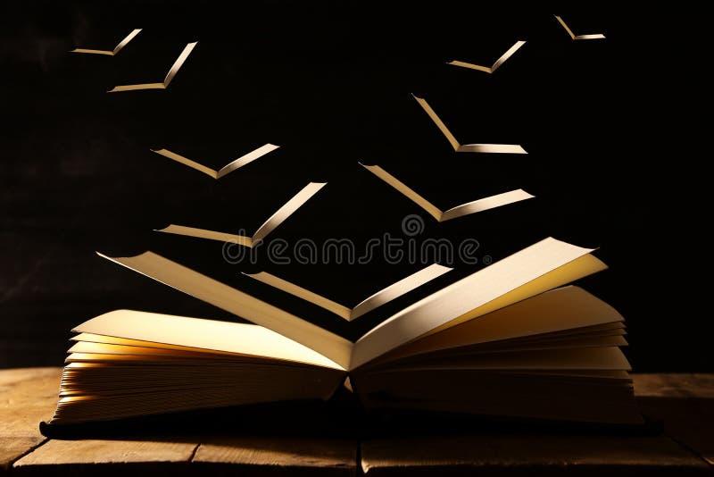 immagine del libro antico aperto sopra la tavola di legno con le pagine di volo immagini stock