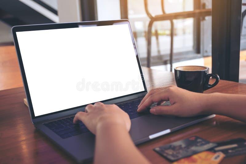 Immagine del modello delle mani che scrivono sulla tastiera del computer portatile con lo schermo e le carte di credito bianchi i immagini stock libere da diritti