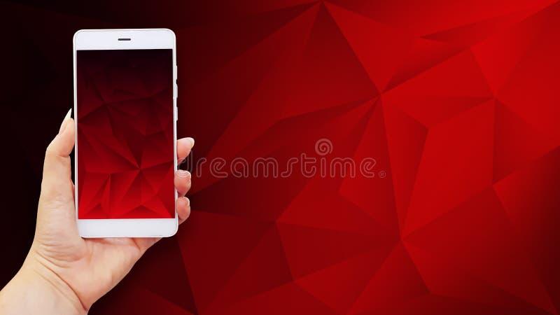 Immagine del modello delle mani che tengono telefono cellulare bianco con lo schermo rosso fotografie stock