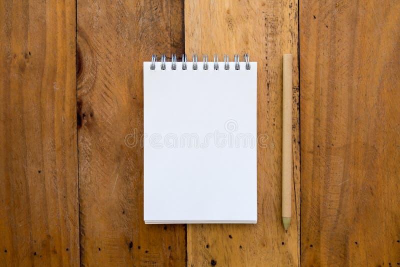 Immagine del modello di vista superiore del taccuino e della matita su di legno d'annata fotografia stock