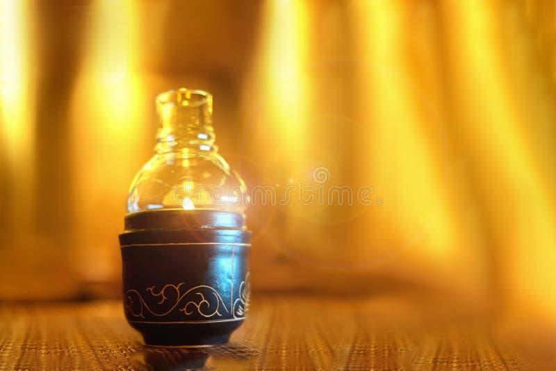 Immagine del primo piano dei supporti di candele di una bottiglia di vetro sulla tavola di legno fondo giallo del fuoco, ceramica immagine stock