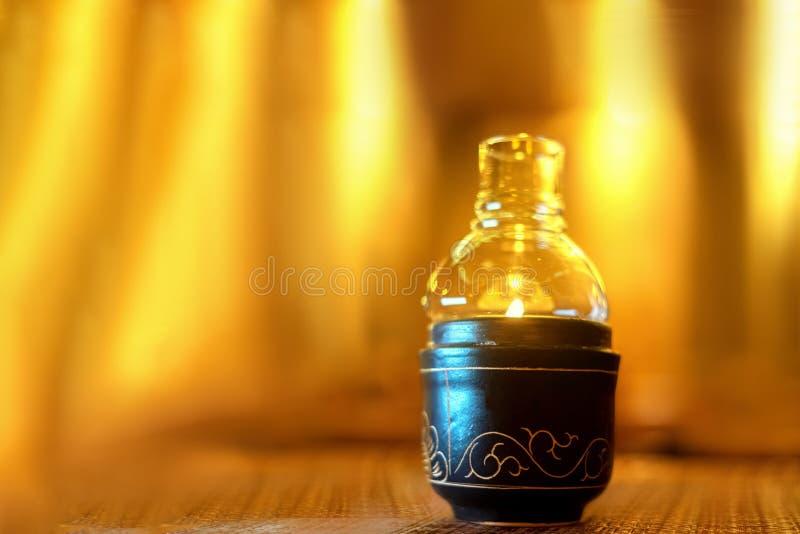 Immagine del primo piano dei supporti di candele di una bottiglia di vetro sulla tavola di legno fondo giallo del fuoco, ceramica immagini stock